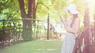Woman using smartphone in the park. Beautiful smiling attractive lady wearing white hat and using modern phone in sunny green outdoors. Communication and technology concept. 4K, DCi, slow motion.