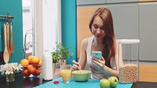 Woman using tablet during breakfast. Filmed in 4K DCi resolution in Slow motion. Beautiful caucasian woman using tablet in the morning in a cozy kitchen.