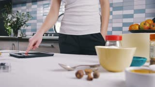 Woman using the tablet at the kitchen, close up, pan