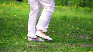 Woman walking in the spring park in slow motion. Close up on feet