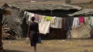 Woman walking with laundry drying in the background