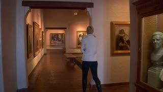 Woman Walks Through Art Gallery
