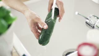 Woman washing courgette under tap water, slow motion shot at 240fps