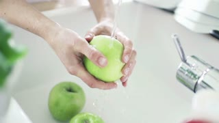 Woman washing green apple under tap water, slow motion shot at 240fps