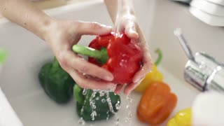 Woman washing red pepper under tap water, slow motion shot at 240fps