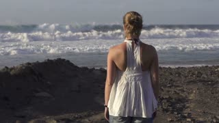 Woman watching at strong waves crashing over the beach, slow motion at 240fps