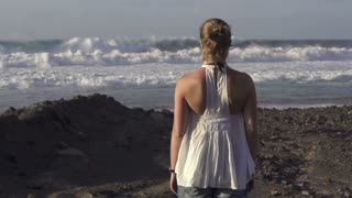 Woman watching at strong waves crashing over the beach, slow motion shot 60fps
