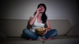 Woman watching movie on couch while eating chips