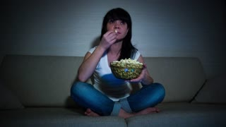 Woman watching movie on couch while eating popcorn