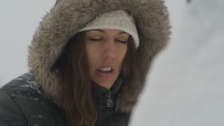 woman wipes face in snowstorm