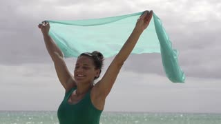 Woman with pareo standing on the beach, slow motion shot at 240fps