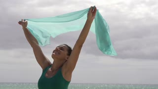 Woman with pareo standing on the beach, slow motion shot at 60fps