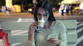 Woman with smartphone sipping coffee at cafe at night