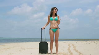Woman with suitcase get lost on the beach