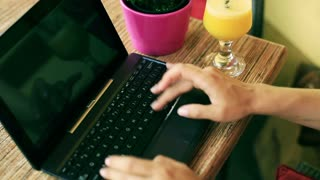 Woman working and typing on laptop keyboard in the street cafe