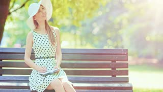 Woman writing in a diary in the green park outdoors, Slow motion. Beautiful lady in a white hat making notes in her notebook, sitting on a bench, smiling and enjoying nature in a summer garden. 4K.