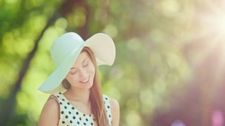 Woman writing in a diary in the green park outdoors, Slow motion. Beautiful lady in a white hat making notes in her notebook, sitting on a lawn, smiling and enjoying nature in a summer garden. 4K.