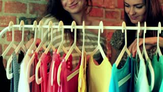 Women looking on colorful clothes in the shop and smiling to the camera