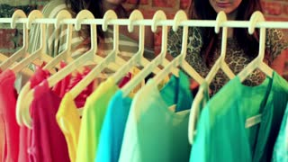 Women talking and looking on the clothes on the hangers
