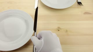 Wooden table. White plates. Hands waiters in white gloves, put a knife and fork