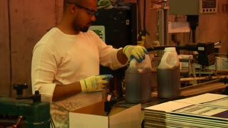 Worker Caps And Packages Chemicals In Gallon Containers