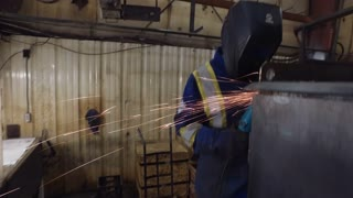 Worker in metal shop using grinder on metal cabinet