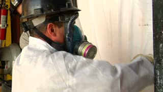 Worker In Respirator Opens Bag Of Chemicals