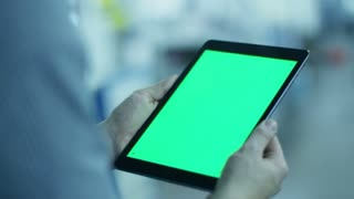 Worker is Holding Tablet PC with Green Screen in Portrait Mode in Factory.  Great For Mock-Up Usage.