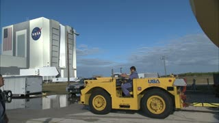 Worker Pulling Equipment with Vehicle Near NASA Building