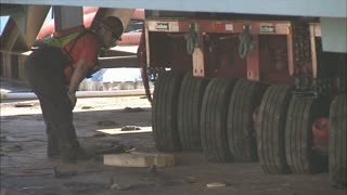 Worker Watching Tires Move