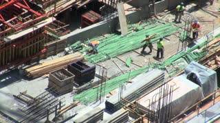 Workers Carry Scraps Through Construction Zone Aerial