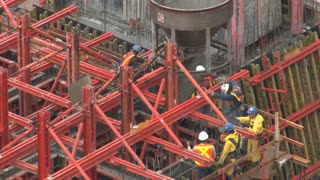 Workers Putting Cement Into Place