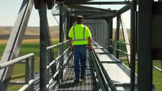 Workers Walk On Elevated Catwalk