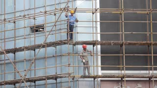 Workers Walking Around on Scaffold