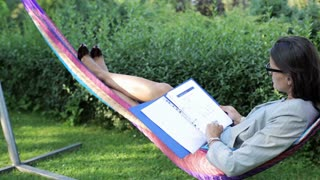 worried businesswoman swinging in hammock and looking at documents