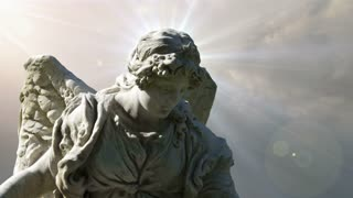 The statue of an Angel on time lapse clouds (Video Loop)