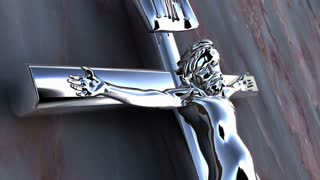 A chrome crucifix in front of a stone wall.