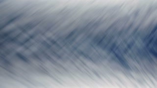 Wispy clouds cross-hatch in a blue sky (Loop)