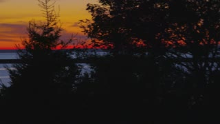 Yellow and Orange Sunset Over Bay Through Trees
