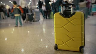 Yellow roll-on bag without owner on the floor at the crowded airport or railway station