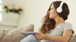 Young adult enjoying music and holding tablet