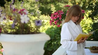 Young adult in a bathrobe standing on the front porch. Girl reading a book and looking at camera
