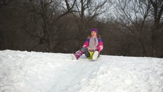 Young adult riding on a sled down the hills