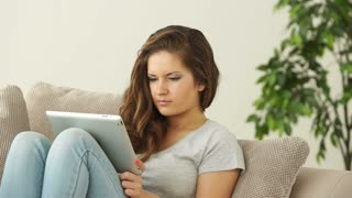 Young adult sitting on sofa with tablet and thinking about something