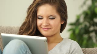 Young adult with touchpad looking at window and smiling