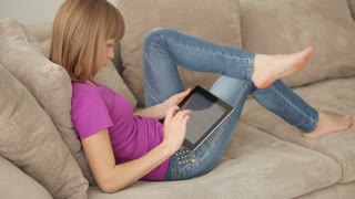 Young adult with touchpad lying on sofa