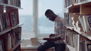 Young African-American man looking through the books sitting on a window sill between stacks in the library