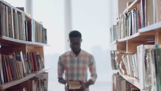 Young African-American man student in glasses wearing checked shirt walking along library bookshelves, then stopping, looking at camera and smiling demonstrating closed books