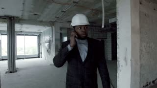 Young african american manager of the construction company goes through the premises of repaired building, talking on the smartphone. This is handsome young man in a business suit and construction