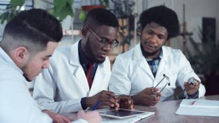 Young African American men doctors in white coats sitting at table in hospital and working with tablet and stethoscope